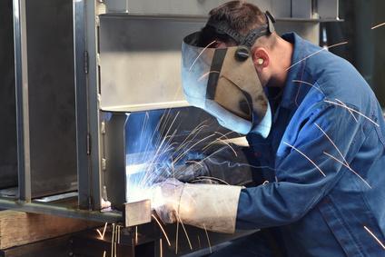 Schweißer arbeitet in der Werkstatt mit Schutzmaske