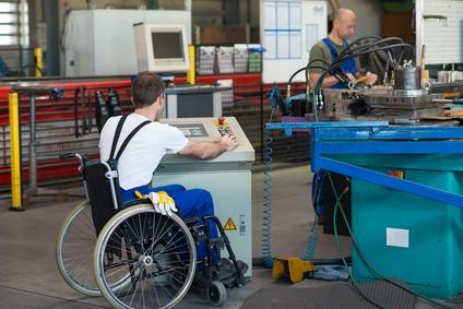 Arbeitnehmer mit Behinderung im Rollstuhl in einer Werkhalle
