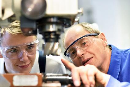 Jugendlicher und Lehrer an einer CNC Maschine