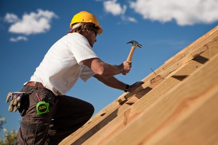 Dachdecker bei der Arbeit mit Schutzhelm