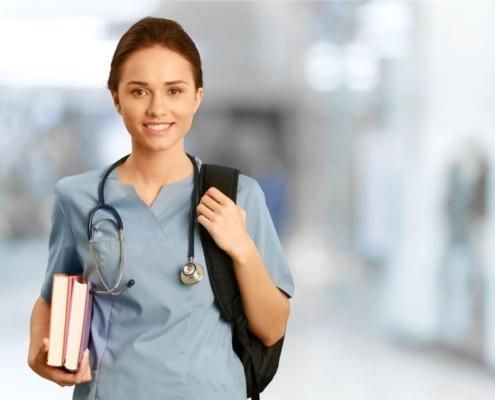 Studentin mit Stethoskop und Lehrbüchern lächelnd