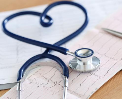 Medizinisches Stethoskop in Herzform verdreht auf Kardiogrammkarte liegend in Nahaufnahme.